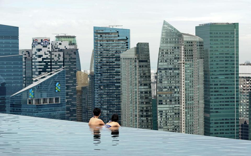 Visitors view the Singapore skyline from the rooftop pool of the Marina Bay Sands resort hotel on May 20.