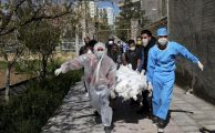 People wearing protective clothing carry the body of a victim who died after being infected with the new coronavirus at a cemetery just outside Tehran, Iran.EBRAHIM NOROOZI/ASSOCIATED PRESS